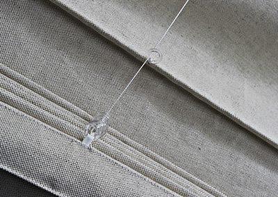 Angewandte Physik für schönes Handwerk: Die Ringe liegen nicht direkt am Stoff, sondern sind mit einem Stofflatz befestigt. Das verschafft den Querstangen das nötige Spiel um sich auszurichten, und so wird auch die Kraft der Schnur mühelos und leicht übertragen.